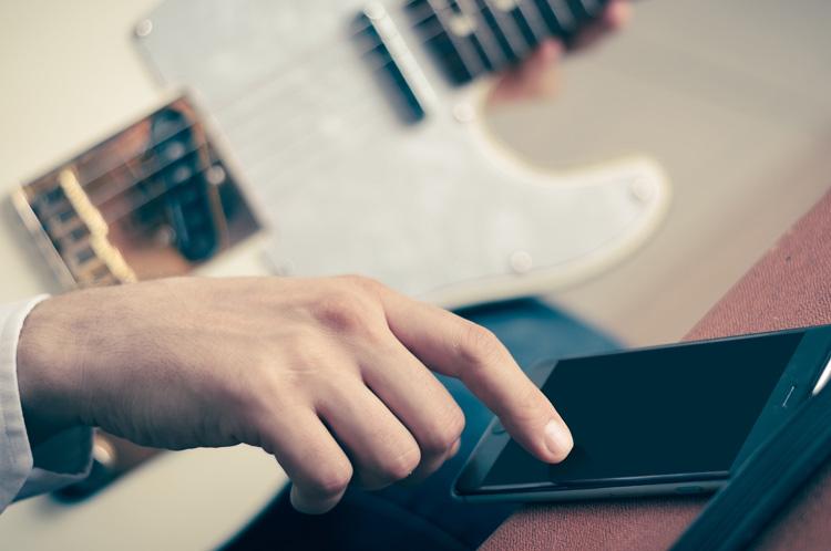 electric guitarist watching shortform video from music brand