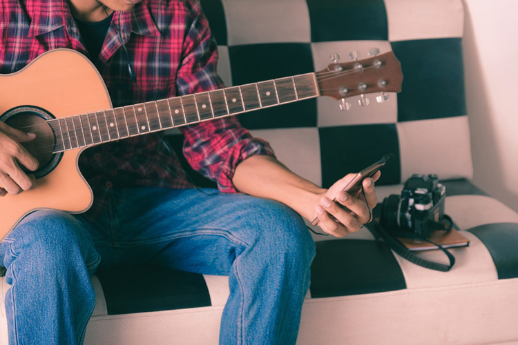 guitarist watching longform video produced by music brand