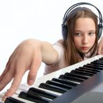 young music student wearing headphones at an electronic keyboard