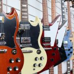 ranks of electric guitars on display in a store