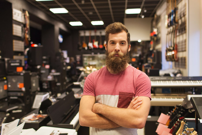 bearded music store dealer with crossed arms standing in front of music equipment and instruments