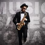saxophonist in tux, hat and sunglasses playing in front of a wall that says music saves today