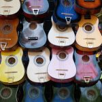 wall of six-string acoustic guitars in a colorful array