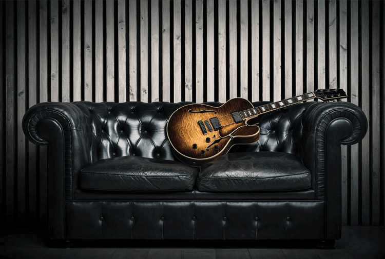 acoustic guitar resting on chesterfield sofa