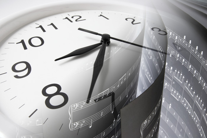 Clock face overlaid with musical score