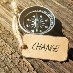 compass with a tag that reads change resting on a rough wooden plank