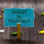 desk top with clothespin holding up a sign that says invest in yourself