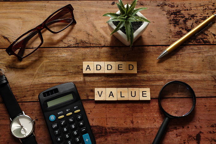 wood desk top with eyeglasses, calculator and other business tools with scrabble tiles spelling out the words added value